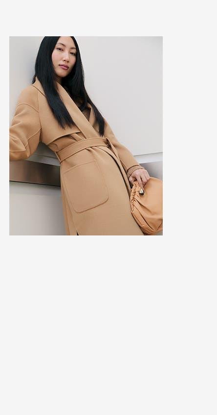 A woman wearing a tan wool coat.