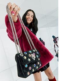A woman holding a jeweled crossbody bag.