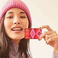 A woman holding a Nordstrom Gift Card.