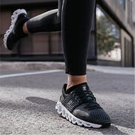 Close-up of a person wearing black On running shoes.