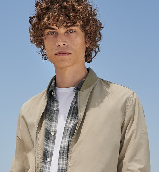 Effortless Outerwear: man in a tan jacket over a plaid flannel shirt.