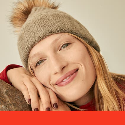 Gifts for her under $50. A woman wearing a knit hat with a furry pompom.