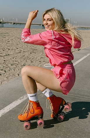 A woman wears a pink matched set from the WAYF '98 collection while roller-skating.
