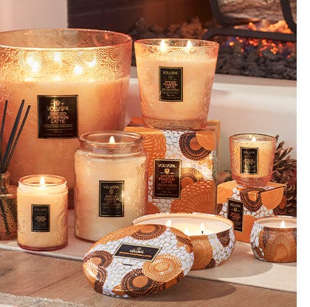 Voluspa spiced pumpkin candles in embossed glass jars and decorative tins.