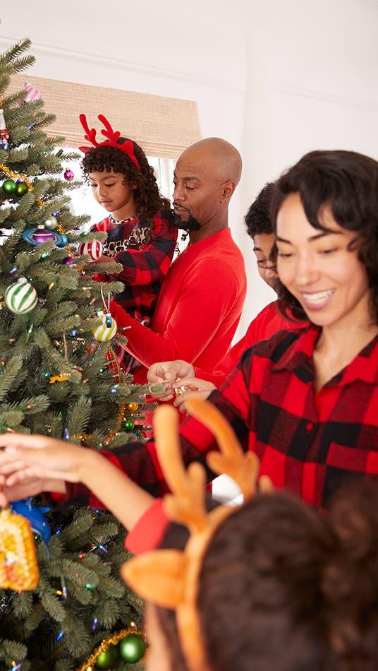 A family wearing festive pajamas decorating their Christmas tree.