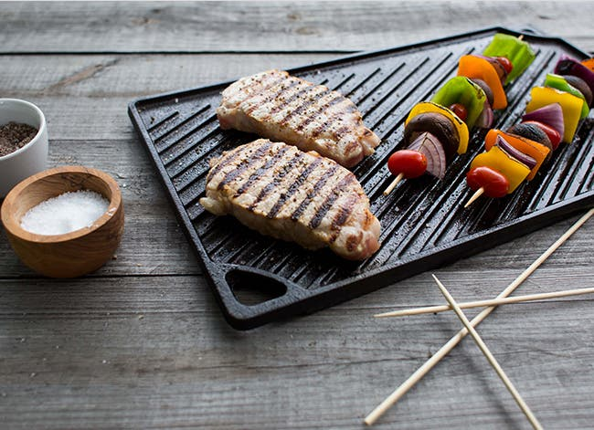 A grill pan with grilled meat and veggie kebobs.