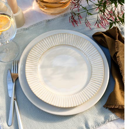 A table setting with dishes, glassware, utensils and linens.