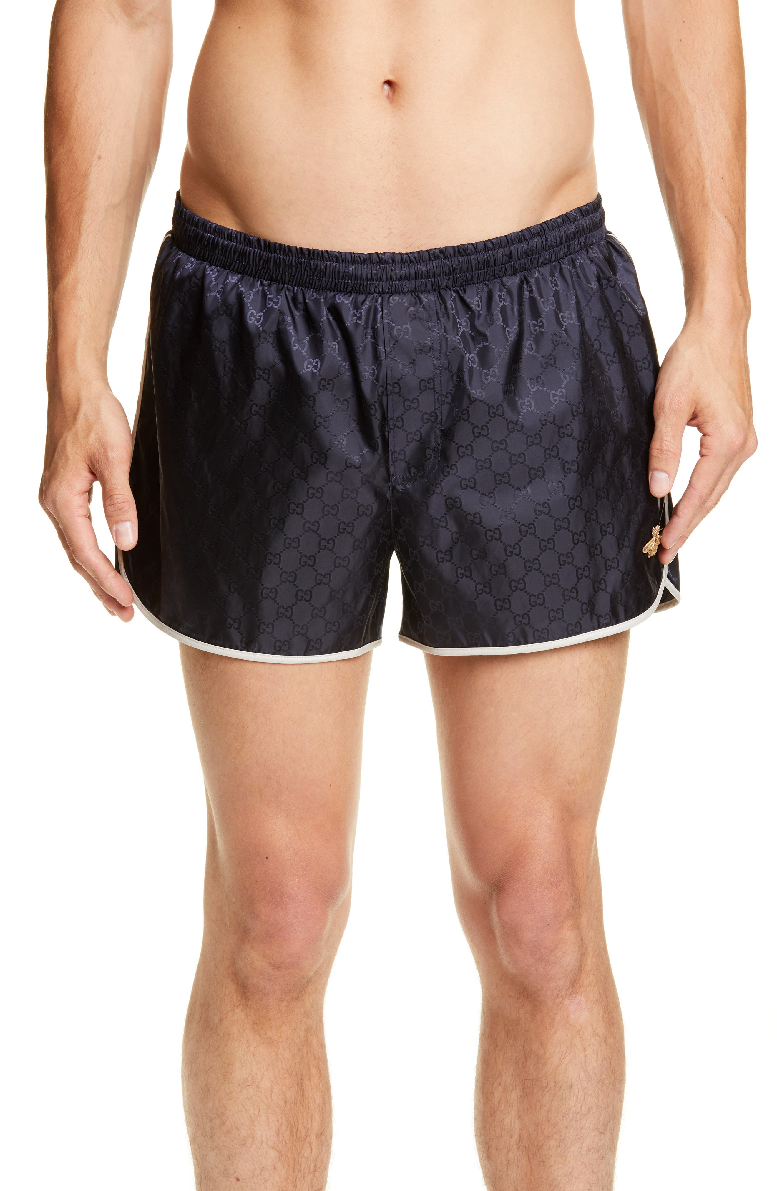 ee044e7bcc Gucci s dark ink-blue GG jacquard swim shorts are cut from a lightweight  quick-drying fabric to a mid-rise with an elasticated waistband.