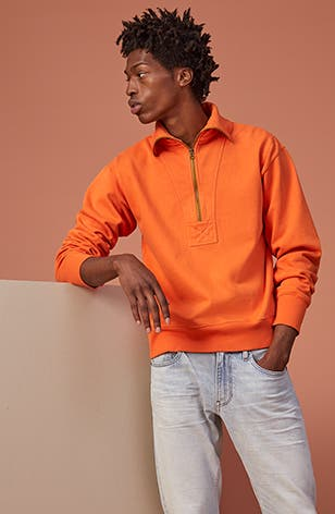 New cozy essentials: man wearing orange half-zip Alex Mill pullover.