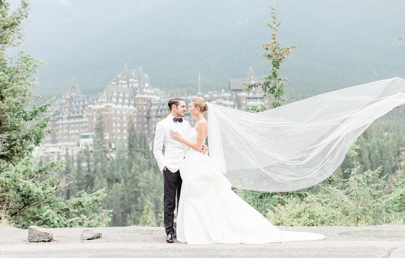Newlyweds Holly and Abraham pose before a castle in the Canadian wilderness.