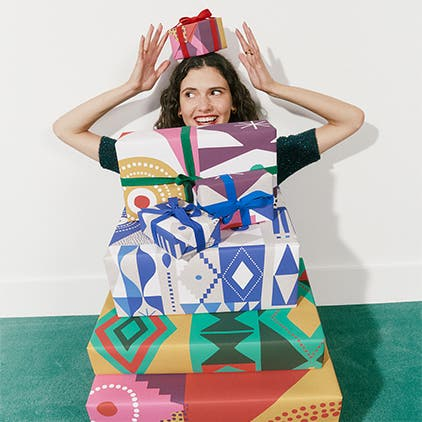 A woman behind a stack of wrapped gifts.