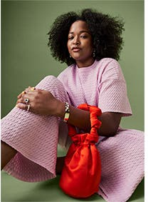 Woman wearing a pink matched set and holding a red bag.
