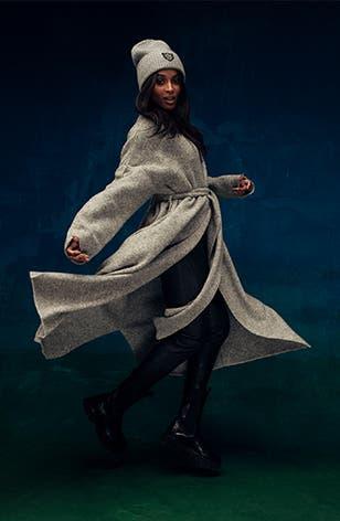 Ciara wears a grey wrap coat with a grey beanie.