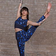 Woman in a boxing stance wearing matching Sweaty Betty sports bra and leggings.