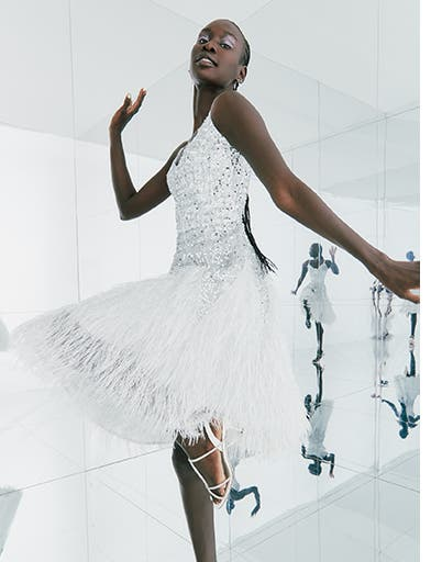 A woman wearing a white special occasion dress with sequins and feathers.