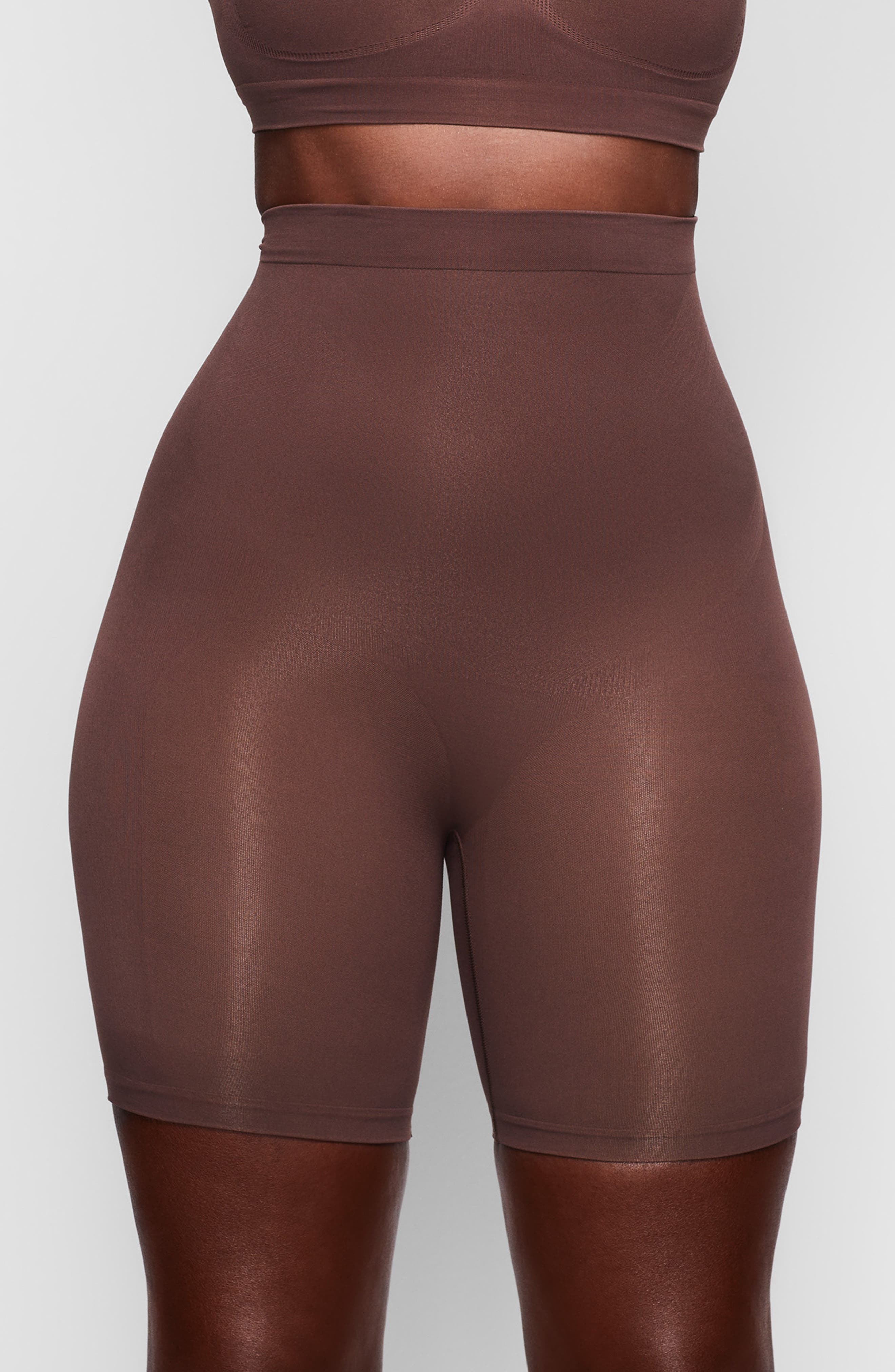 Sculpt your body\\\'s natural shape in mid-thigh shaping shorts with a whisper-soft and seamless design from Kim Kardashian West\\\'s SKIMS. Reflecting the brand\\\'s passion for highly technical shapewear solutions for every body, this staple piece smoothes your upper legs while lifting your butt and comes in nine different shades to complement your skintone. Style Name: Skims Sculpting Seamless Mid Shorts (Regular & Plus Size). Style Number: 6013499.
