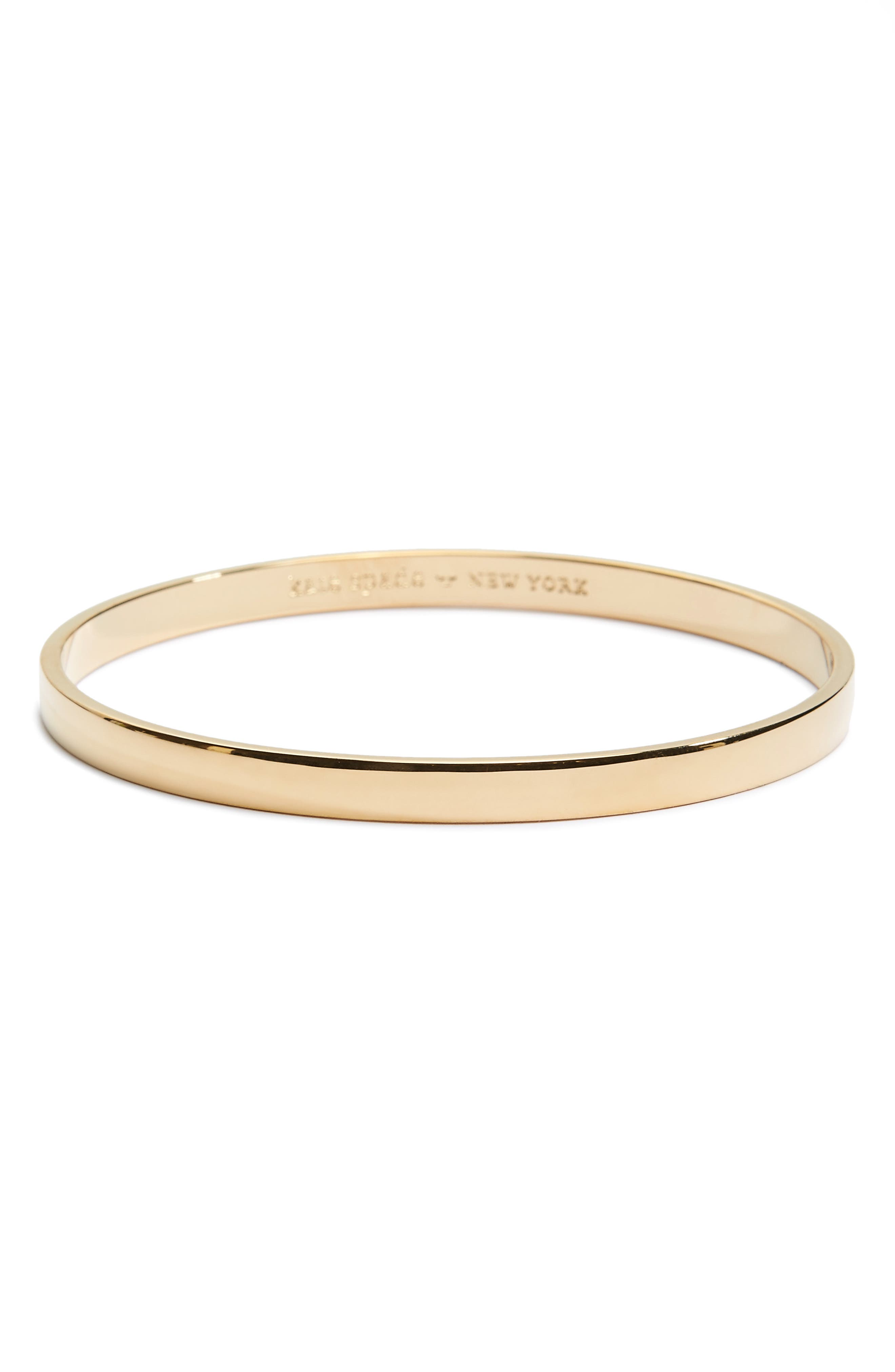 A slim, stackable bangle plated in lustrous 12-karat gold hides a meaningful \\\