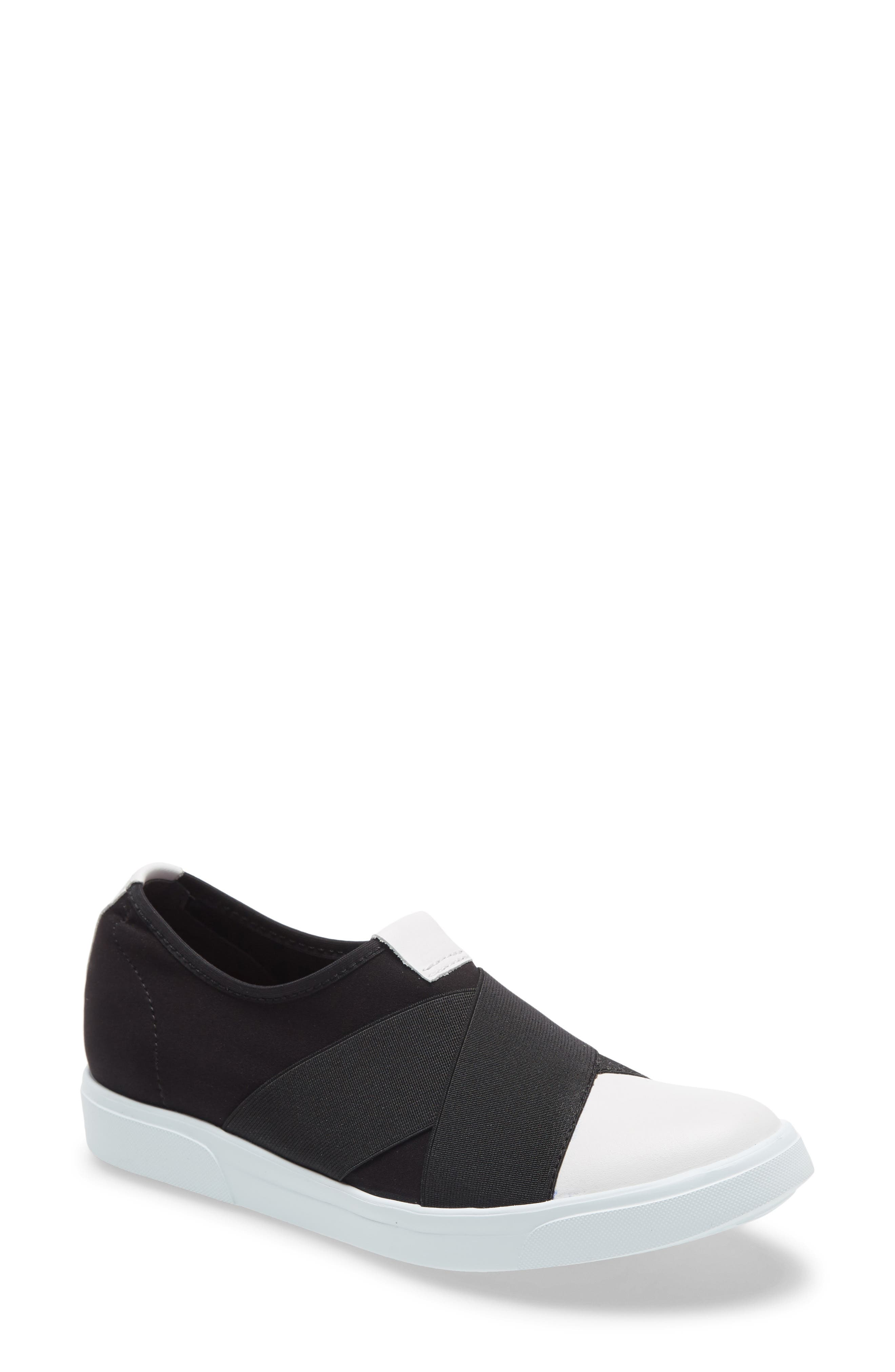 This versatile black-and-white sneaker with wide elastic straps comforts as you trek about with its breathable and moisture-wicking lining. Style Name: Munro Anjela Slip-On Sneaker (Women). Style Number: 5994415. Available in stores.