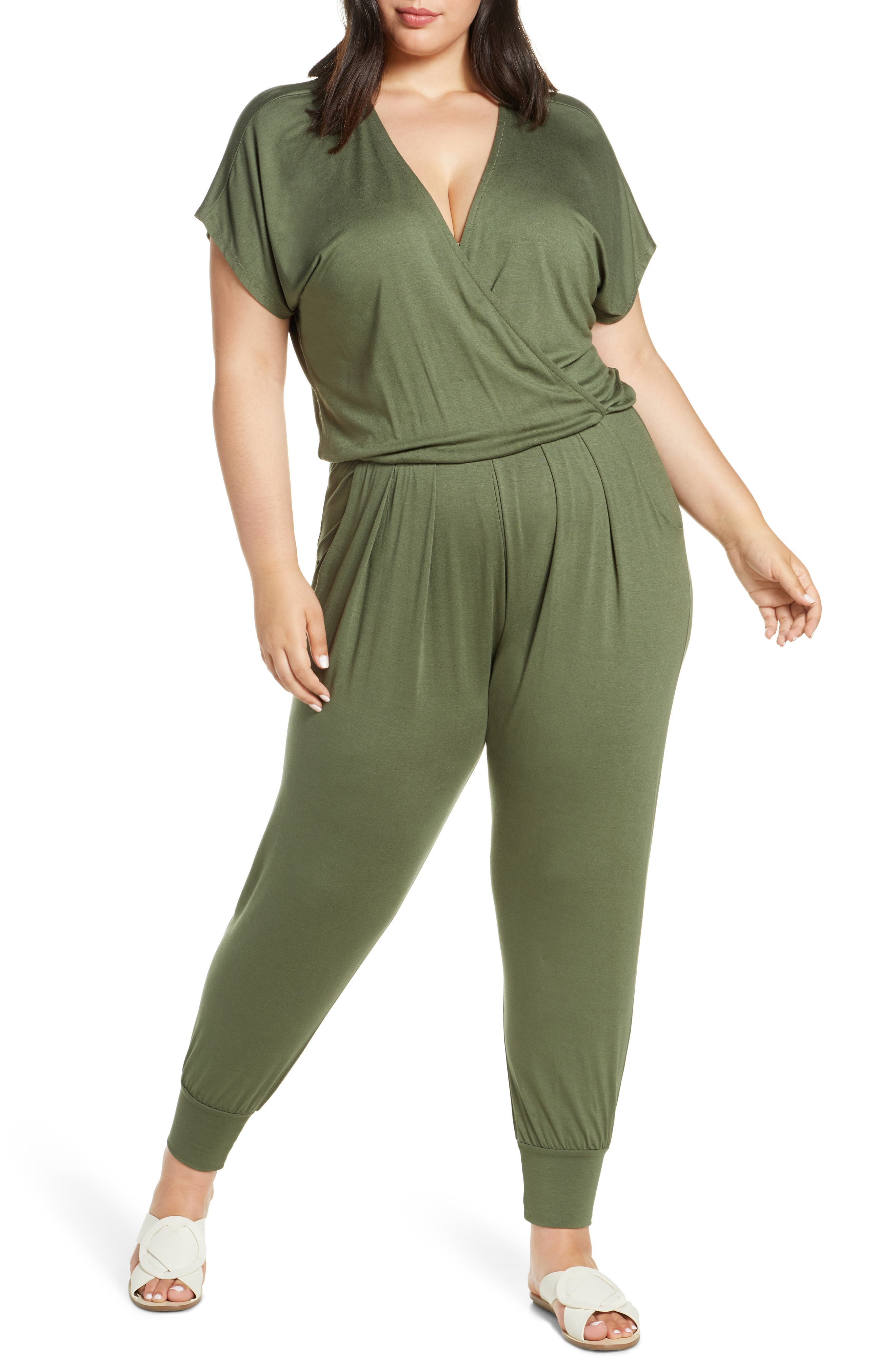 Cut from soft, supple jersey, this ready-for-anything jumpsuit features a deep surplice neckline and pleat-front pants that end in tapered, banded cuffs. Style Name: Loveappella Short Sleeve Wrap Top Jumpsuit (Plus Size). Style Number: 5614801. Available in stores.