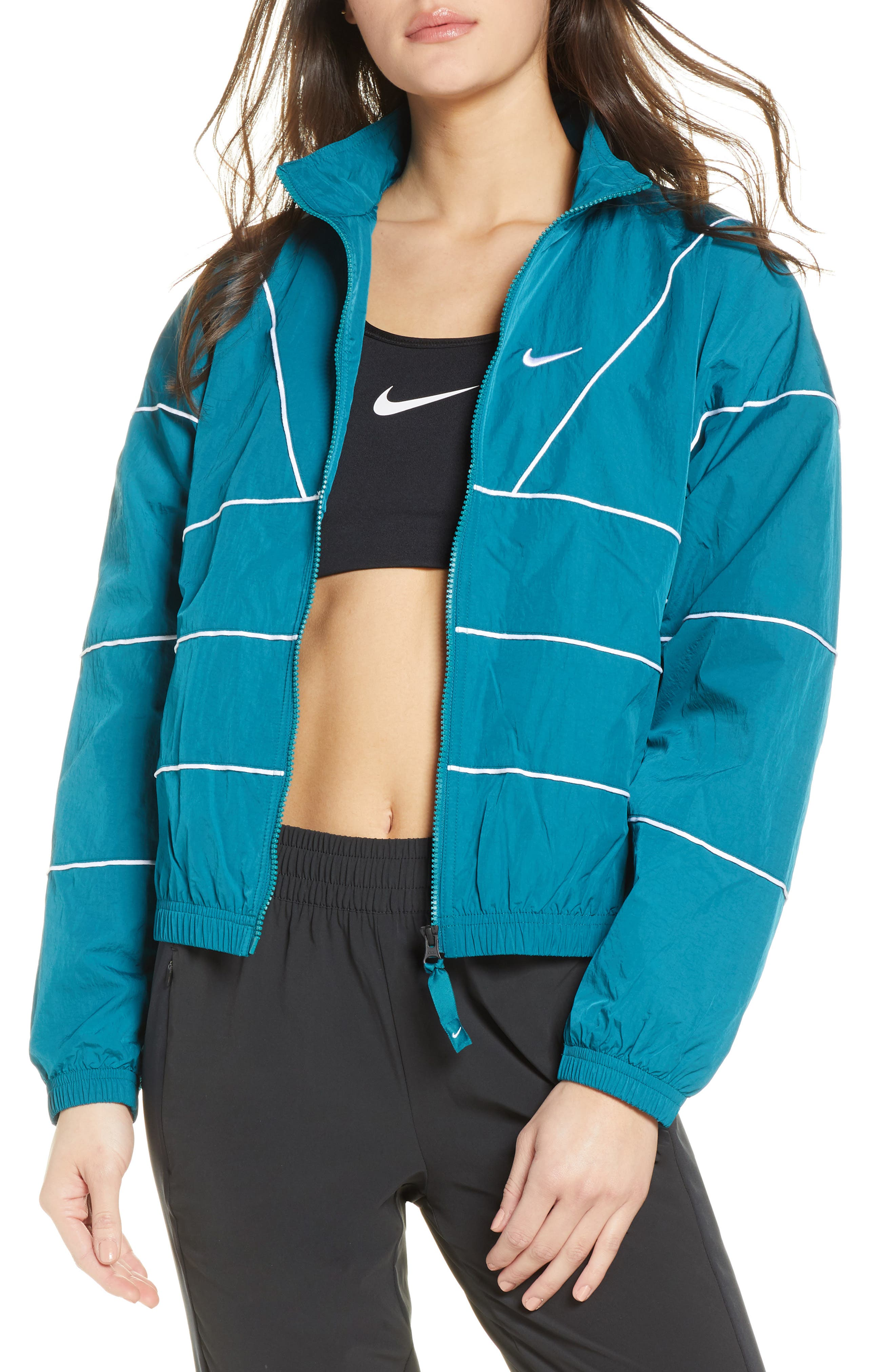 Throwing back to vintage track designs, this soft nylon jacket has contrast binding and reflective details so everyone can clearly see your cool look. A mesh lining ensures comfortable breathability, while the elastic cuffs and hem keep in warmth. Style Name: Nike Women\'s Track Jacket. Style Number: 5958096. Available in stores.