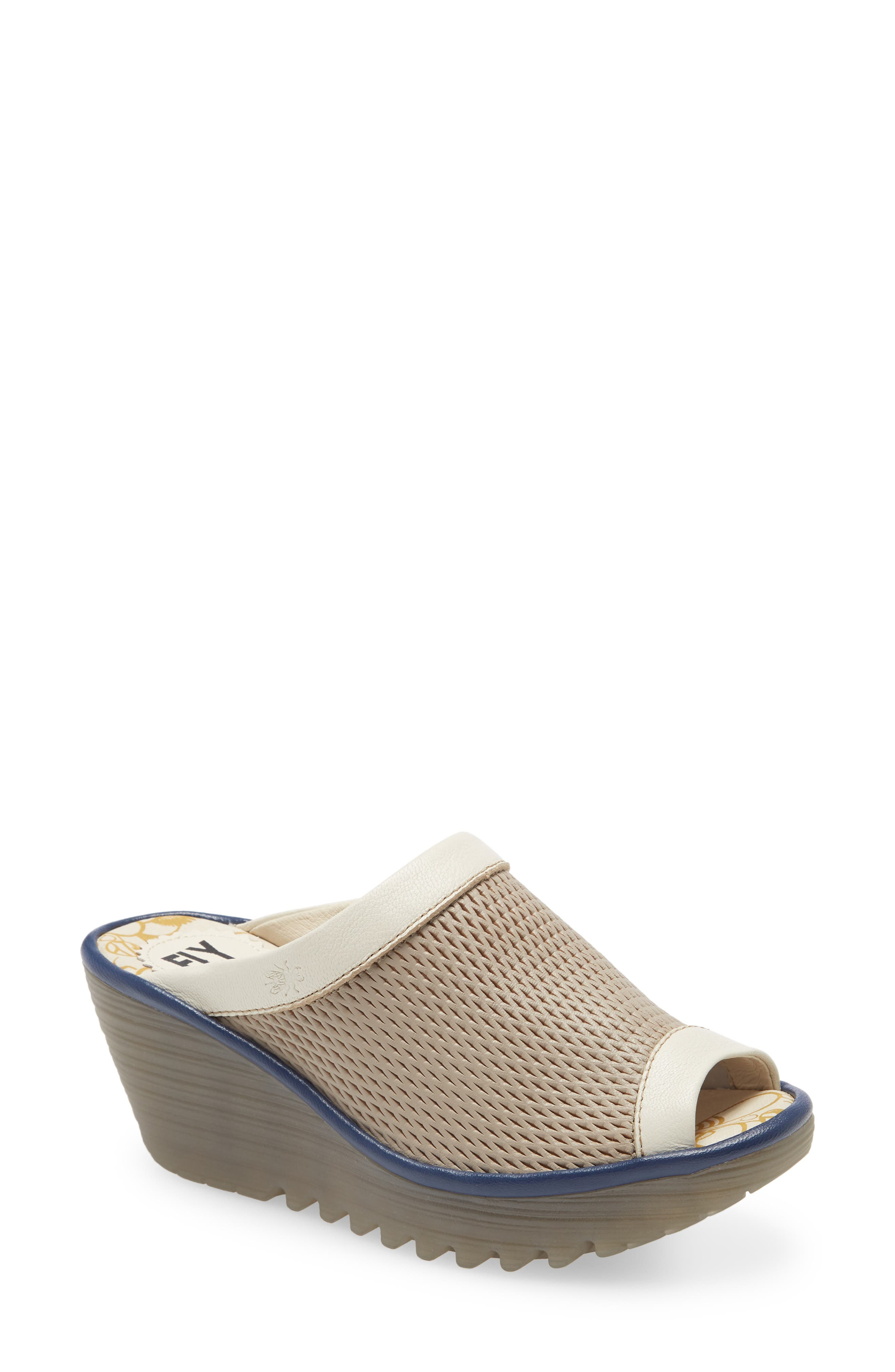 Latticed perforations add breathability to a foam-cushioned slide sandal lifted by the brand\\\'s signature, sporty textured wedge and platform. Style Name: Fly London Yeno Wedge Slide Sandal (Women). Style Number: 6002340. Available in stores.