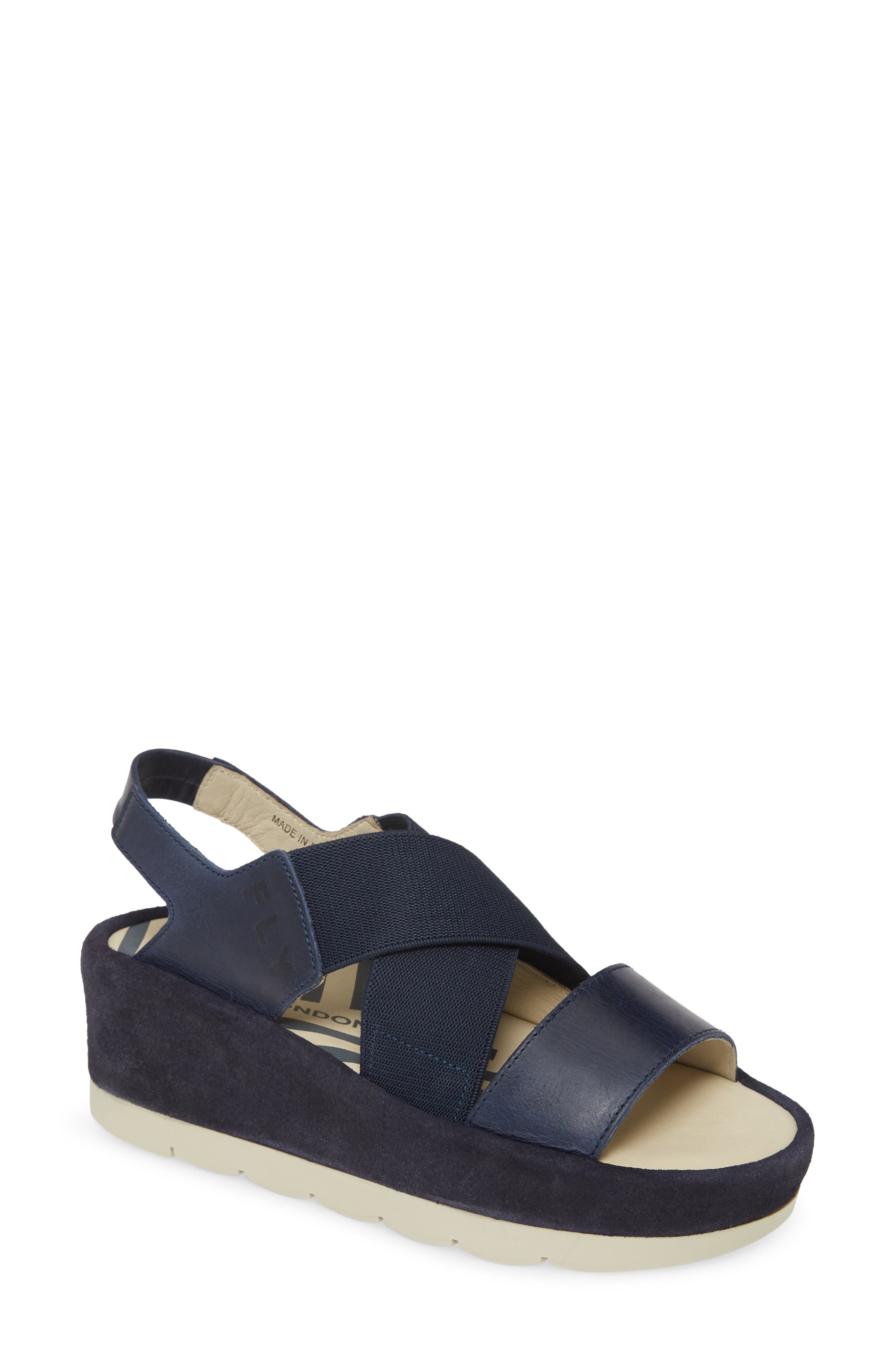 Wide elastic straps crisscross at the top of a slingback sandal lifted by a stable one-piece wedge and platform. Style Name: Fly London Bime Wedge Sandal (Women). Style Number: 6002359. Available in stores.
