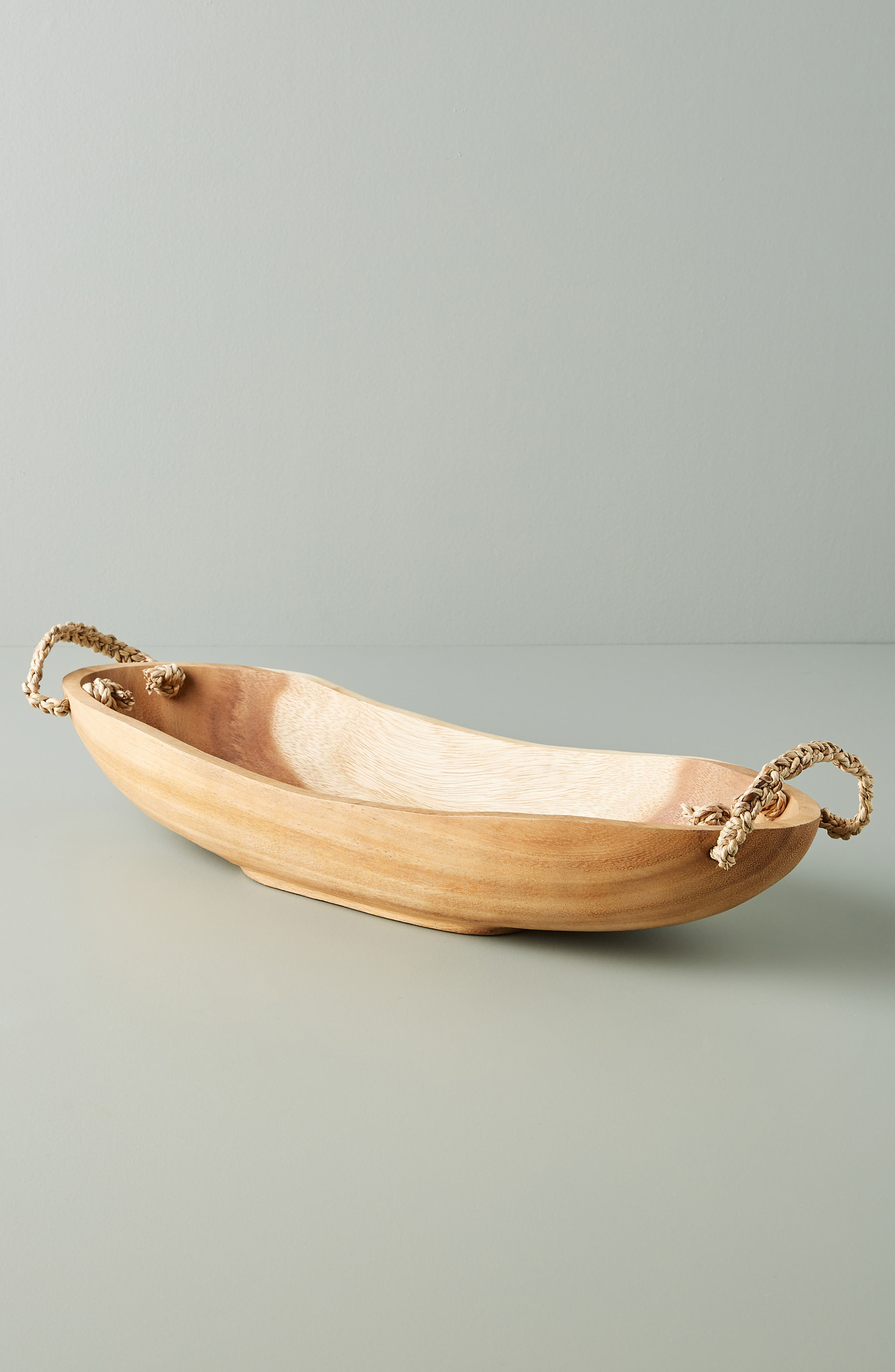 Hand carved from solid acacia wood with woven rope handles, this elongated bowl makes an elegant way to display fruit and more. Style Name: Anthropologie Home Olmena Serving Bowl. Style Number: 5998641. Available in stores.
