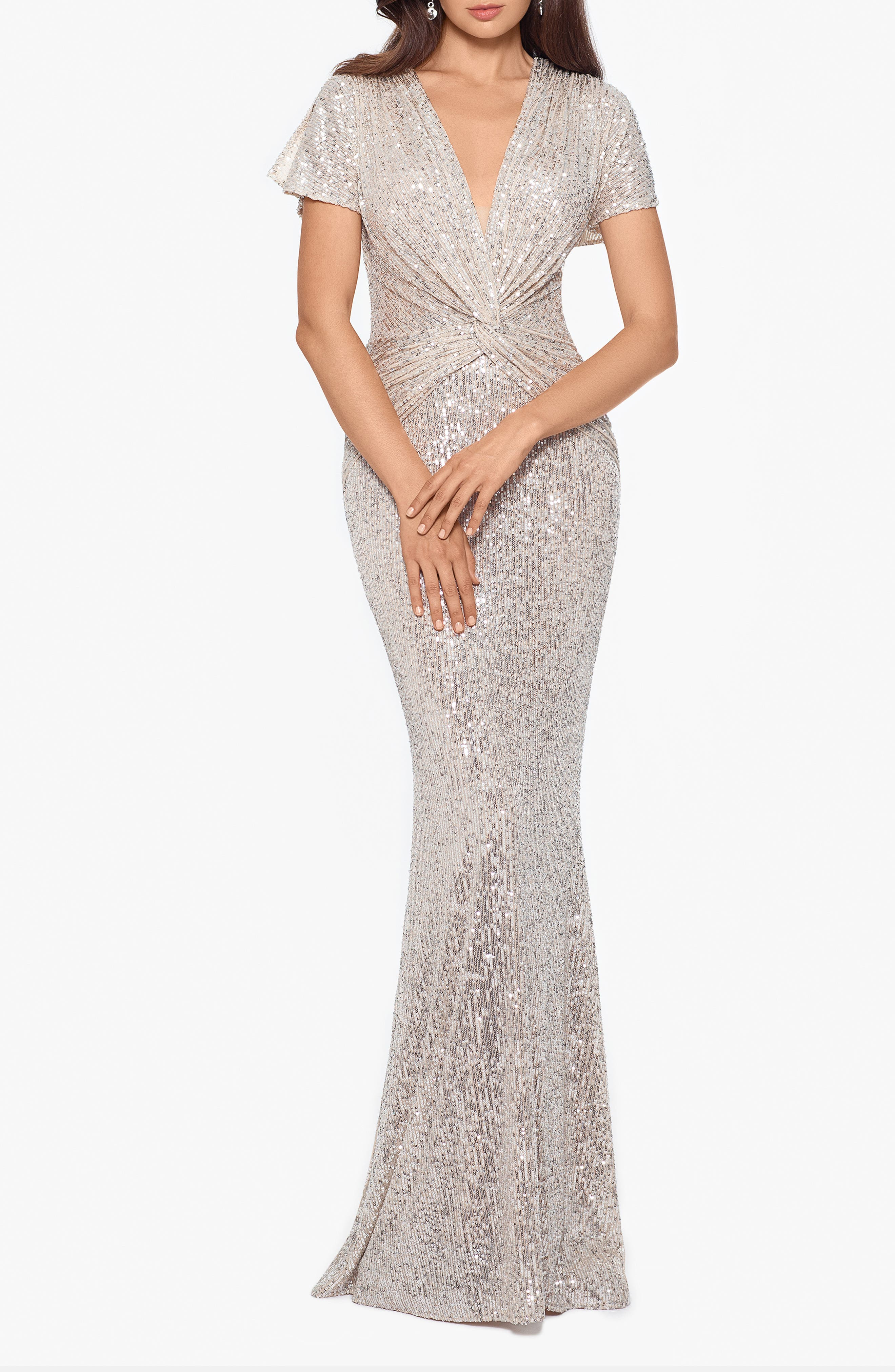 Dolman sleeves gracefully flow into the twist-front waist on this glittering mermaid gown, creating a sleek silhouette and a seductively plunging neckline. Style Name: Xscape Sequin Twist Front Mermaid Gown. Style Number: 5954046. Available in stores.