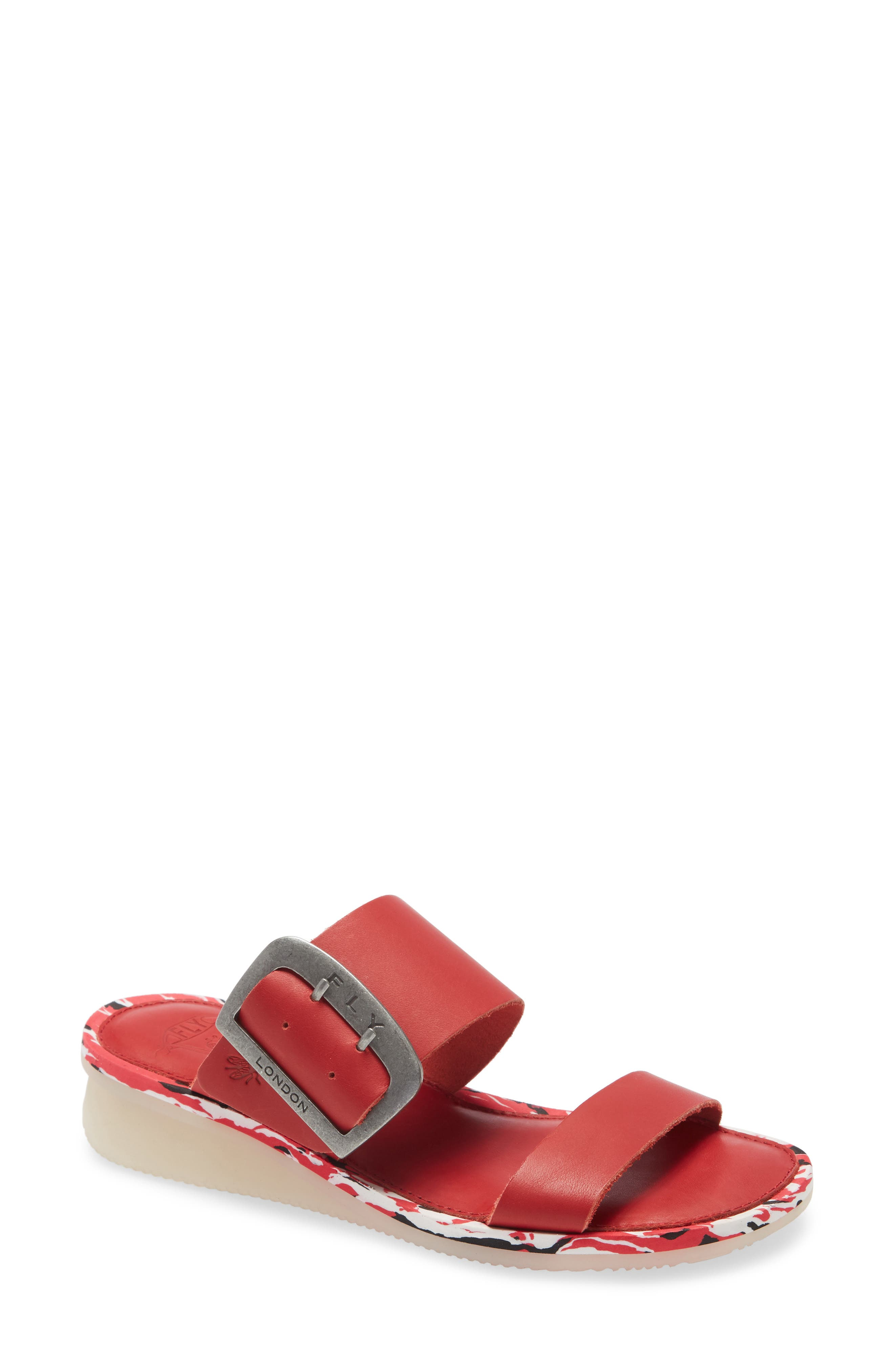 An oversized, logo-etched buckle secures the wide arch strap of a double-band slide sandal lifted slightly with a low wedge. Style Name: Fly London Cape Slide Sandal (Women). Style Number: 6002355. Available in stores.