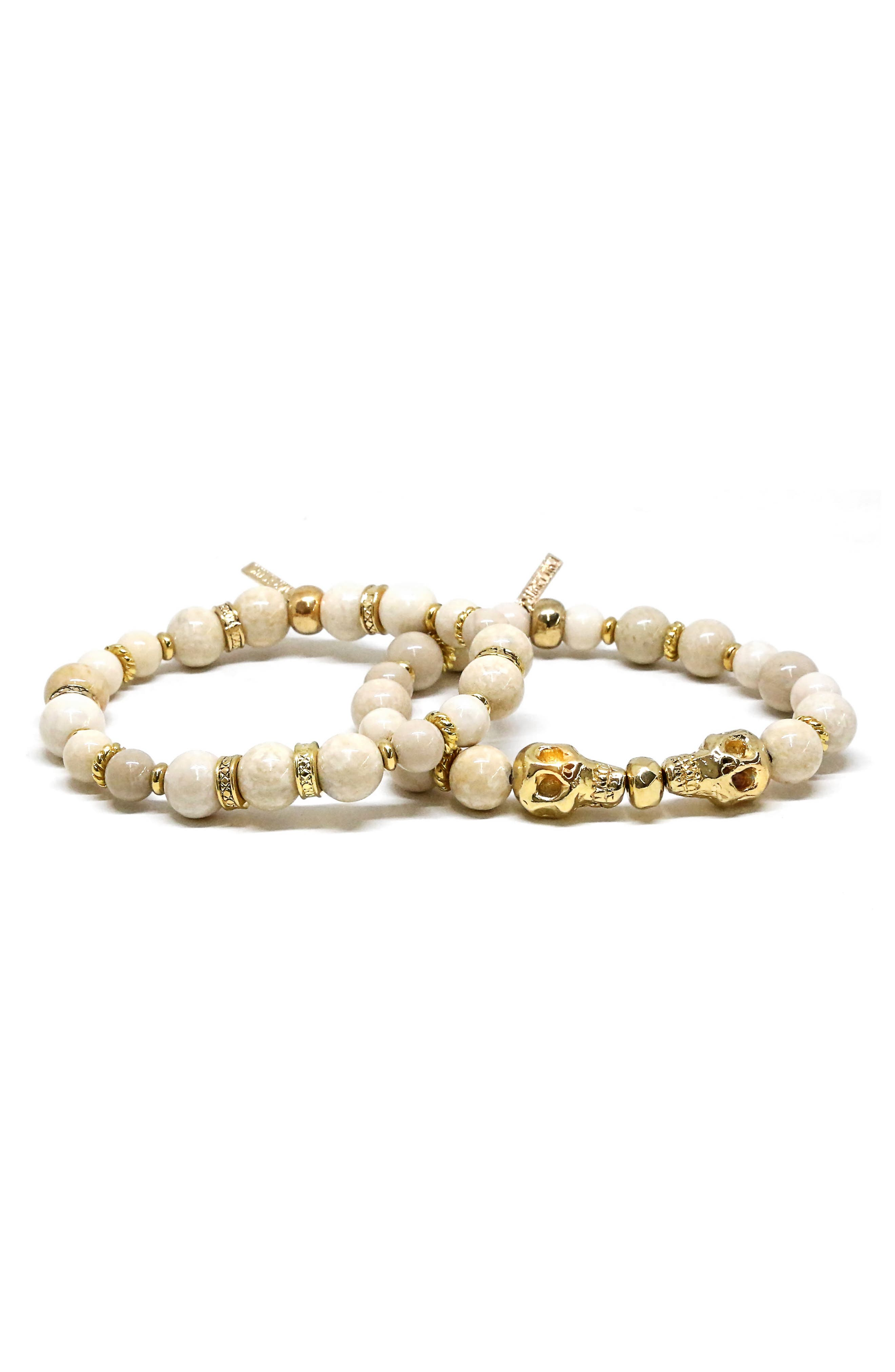 Textured golden accents and polished skull charms add intrigue to this set of bracelets featuring howlite beads, a mineral believed to alleviate stress. Style Name: Ettika Mr. Ettika Set Of 2 Howlite Skull Stretch Bracelets. Style Number: 6172941. Available in stores.