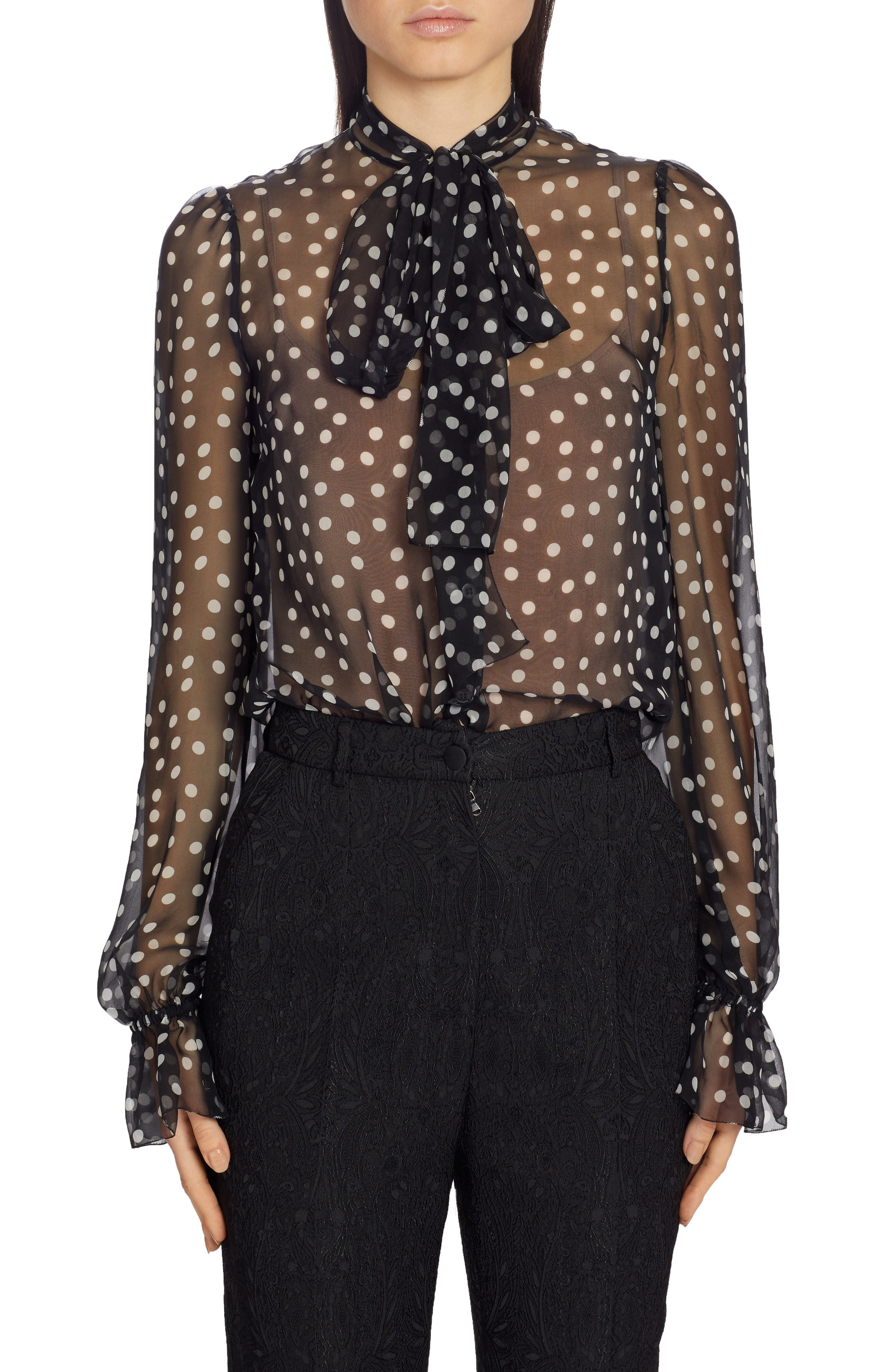 Polka dots pepper the diaphanous silhouette of this jaunty tie-neck blouse framed with billowy flounce-cuff sleeves. Style Name: Dolce & gabbana Polka Dot Sheer Chiffon Blouse. Style Number: 5933259. Available in stores.