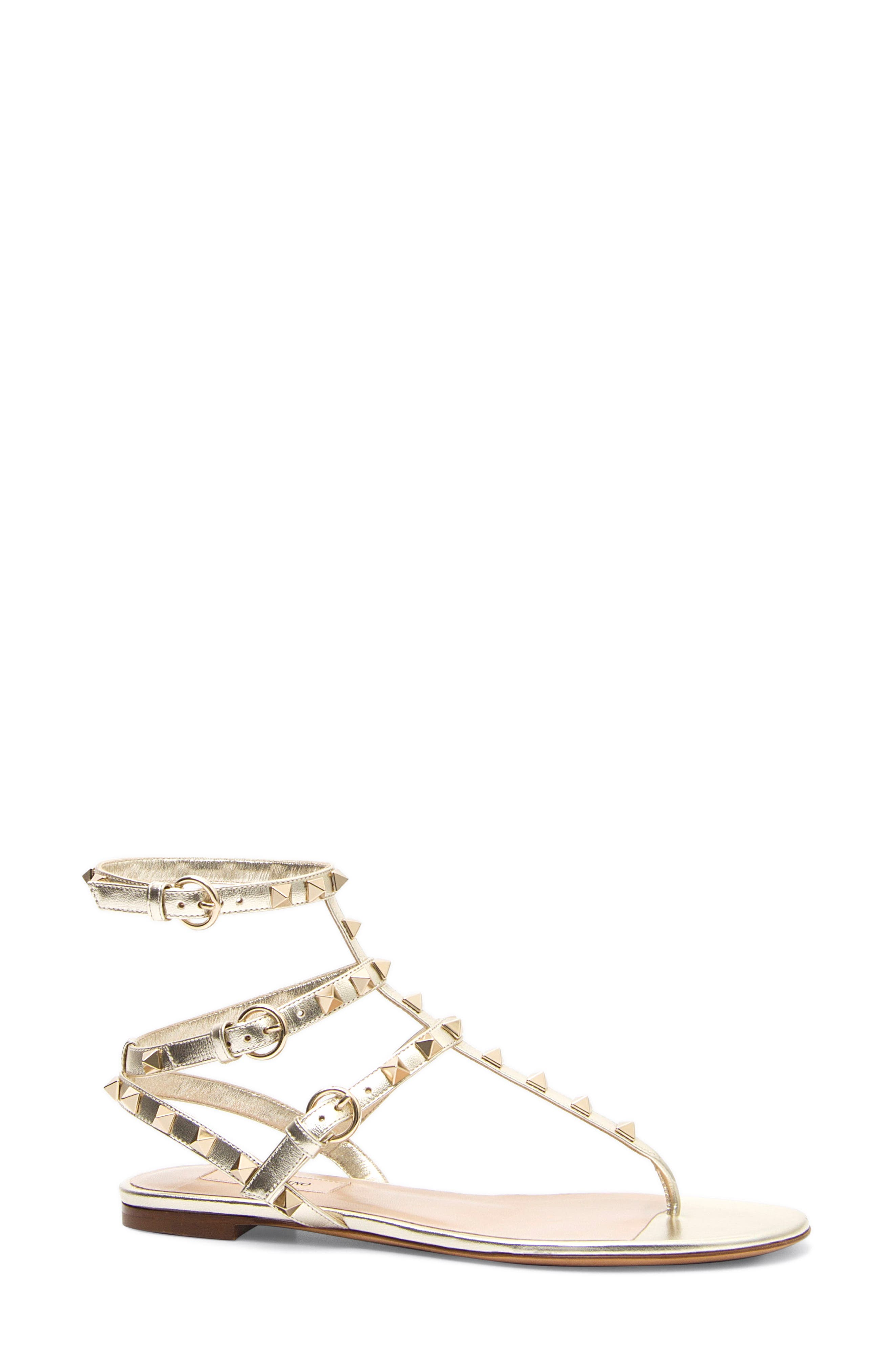 Valentino\'s signature gilded pyramid studs multiply the shine on a cage sandal shaped from shimmery calfskin leather. Style Name: Valentino Garavani Rockstud Metallic Thong (Women). Style Number: 5429286. Available in stores.