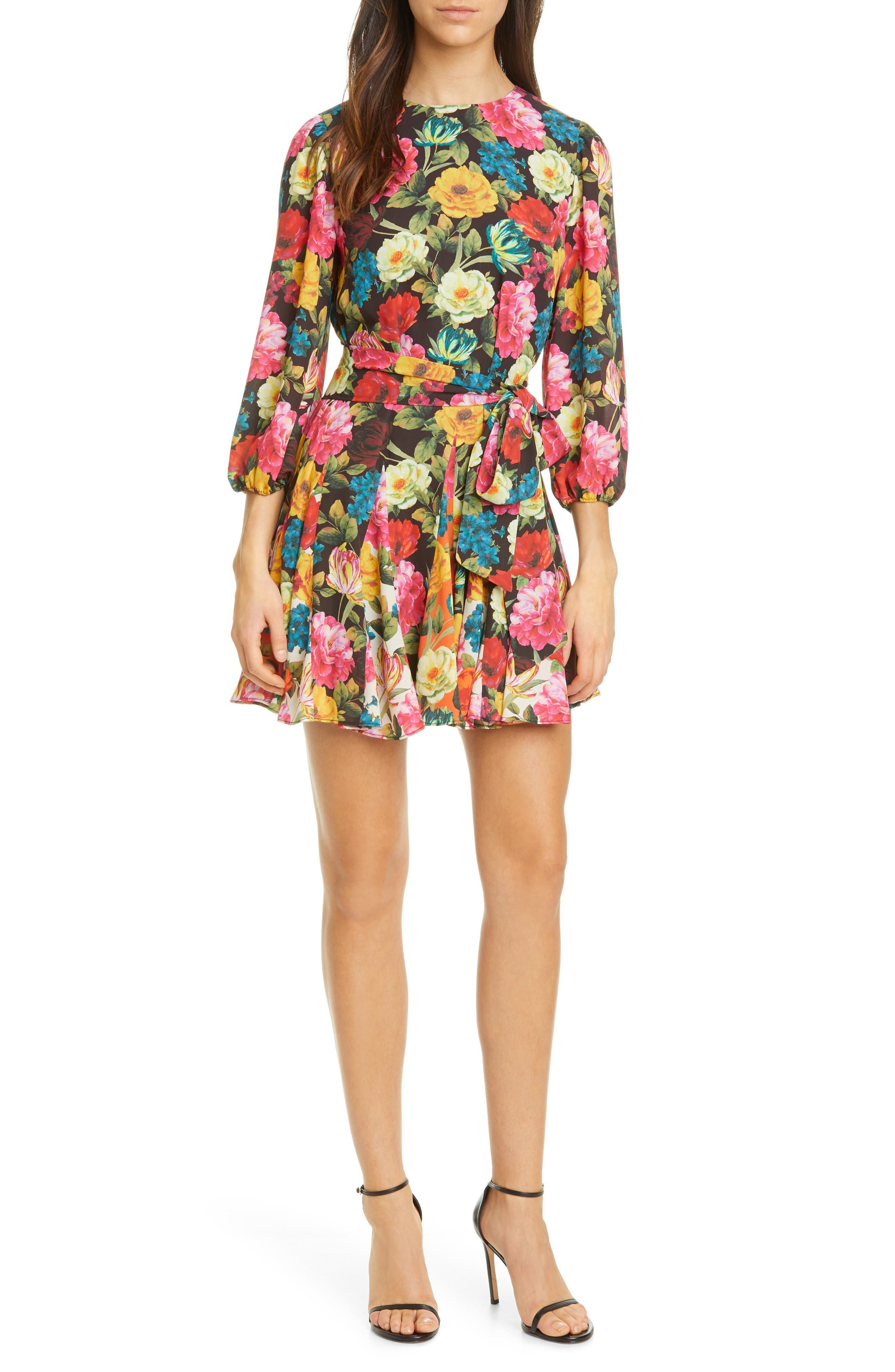 A floaty georgette dress captivates in a vivid floral print painted on a black background and accented in a colorfully backed floral print on the godet insets. Style Name: Alice + Olivia Mina Floral Belted Minidress. Style Number: 6014403. Available in stores.