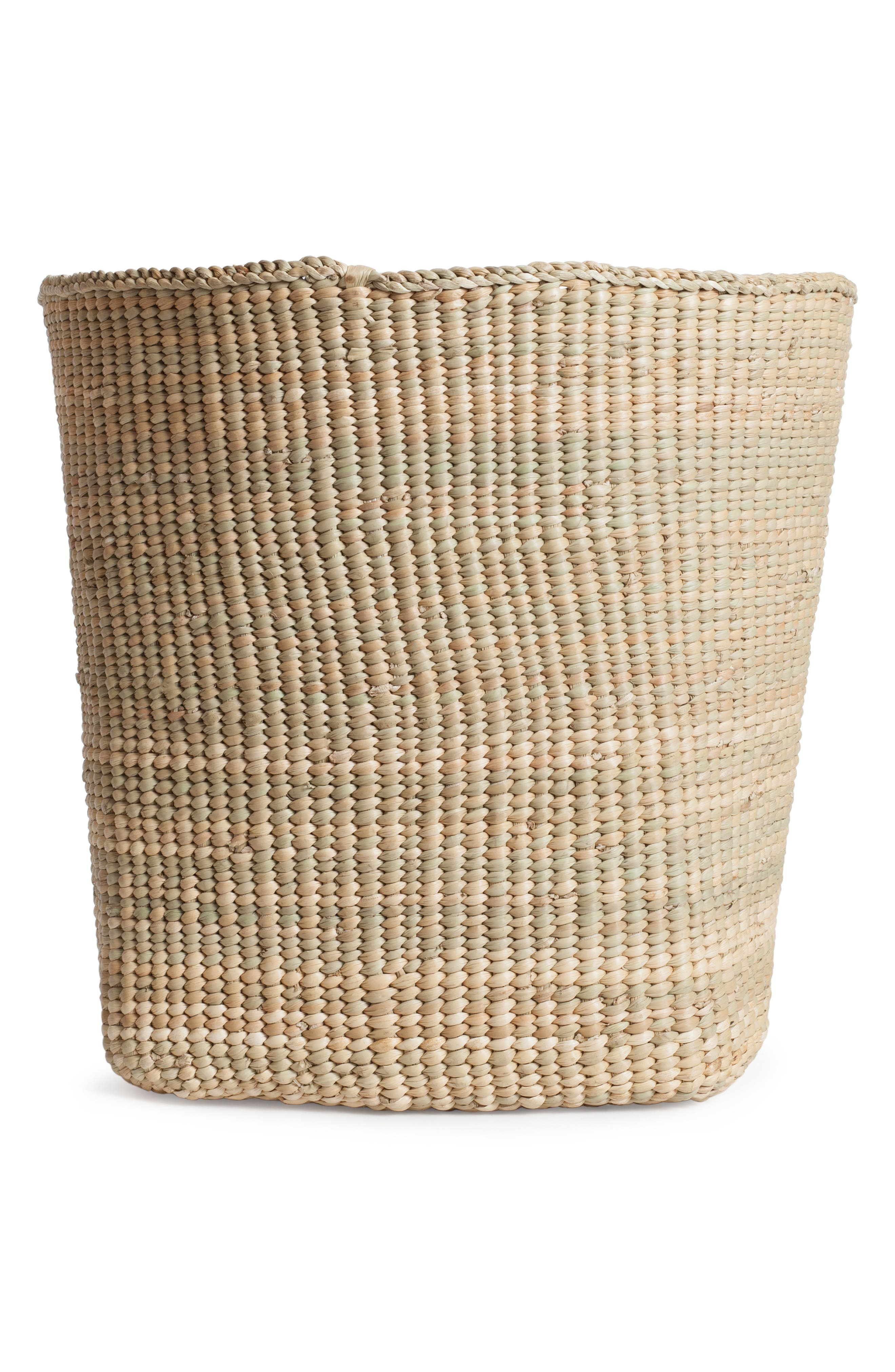 Useful as a garbage bin or small plant cachepot, this short basket is handwoven by Tanzanian artisans in a traditional shape using local dried grass. Style Name: Hawkins New York Short Woven Grass Basket. Style Number: 6100256. Available in stores.